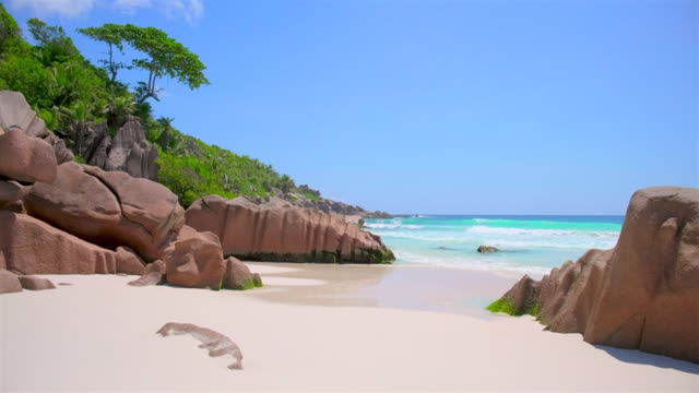 beautiful tropical beach petite anse with sculpted granite rocks and palm trees - island of la digue, seychelles, indian ocean islands. - seychelles stock videos & royalty-free footage