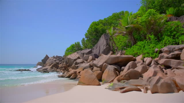 beautiful tropical beach petite anse with sculpted granite rocks and palm trees - island of la digue, seychelles, indian ocean islands. - exoticism stock videos & royalty-free footage