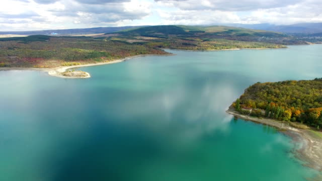 aerial: beautiful turquoise lake between wooded hills - chiaroscuro stock videos and b-roll footage