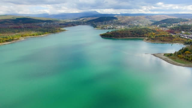aerial: beautiful turquoise lake with nearby small town - chiaroscuro stock videos and b-roll footage