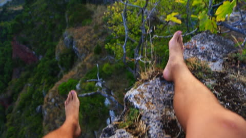 beautiful view of traveler guy contemplating the unique town of siurana in the tarragona mountains sitting on the edge during sunset summer with church on the top and landscape view. - human leg stock videos & royalty-free footage