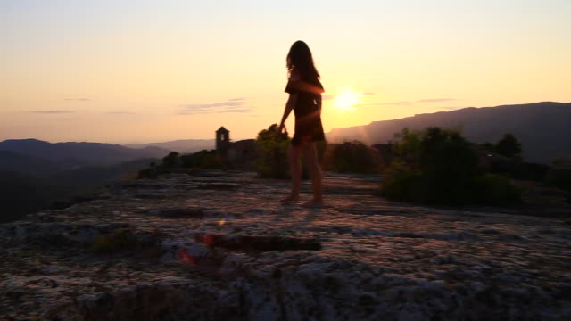 beautiful view of traveler woman contemplating the unique town of siurana in the tarragona mountains during sunset summer with church on the top and landscape view. - 崖点の映像素材/bロール