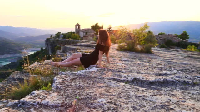 Beautiful view of traveler woman contemplating the unique town of Siurana in the Tarragona mountains during sunset summer with church on the top and landscape view.