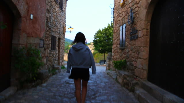 stockvideo's en b-roll-footage met beautiful view of traveler woman walking in the unique town of siurana in the tarragona mountains during summer vacations in the catalonia region. - shirt met capuchon
