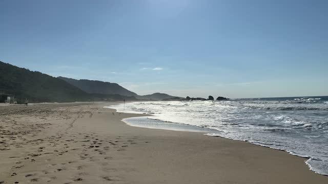晴れた日の空のビーチでの波と砂の美しい景色。 - sunny点の映像素材/bロール