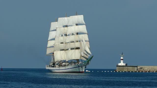 schöne vintage segelboot kommt in den hafen auf dem hintergrund eines leuchtturms - historisch stock-videos und b-roll-filmmaterial