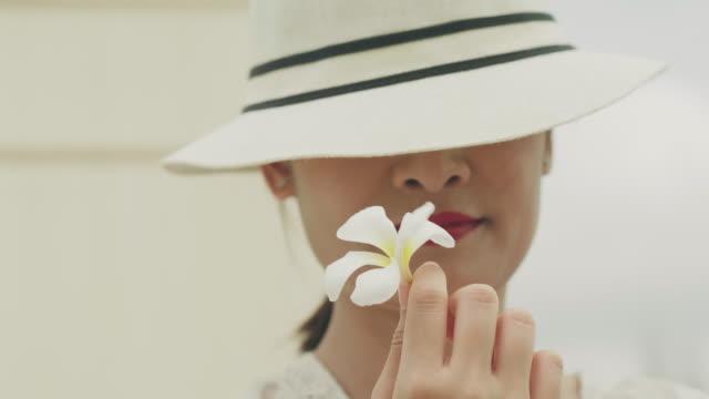 Belle visiteur portant chapeau blanc transporte fleur blanche