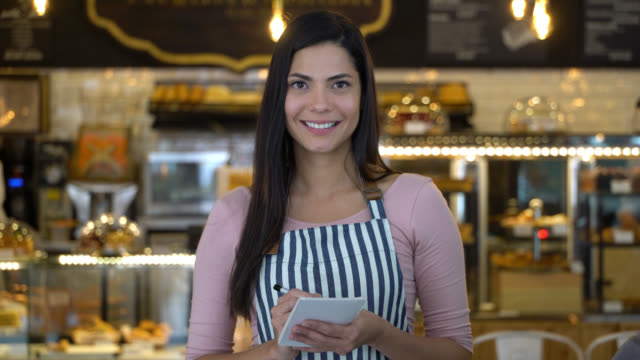 beautiful waitress at a bakery holding a notepad and facing camera smiling - bakery stock videos and b-roll footage