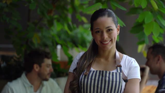 vackra servitris tittar på kameran mycket vänlig leende medan kunder sitter i bakgrunden - servitris bildbanksvideor och videomaterial från bakom kulisserna