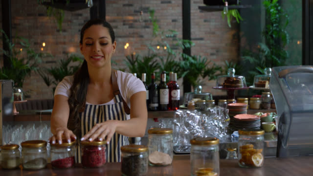 beautiful waitress organizing the jars on counter at a restaurant looking very happy - comparison stock videos and b-roll footage