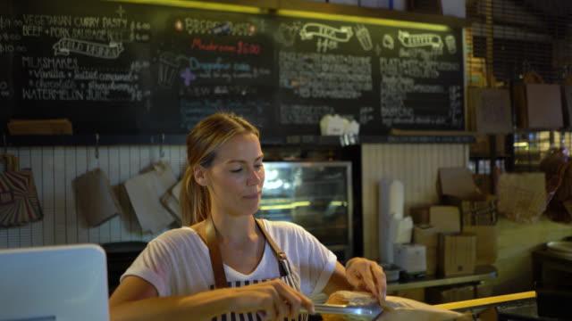 vidéos et rushes de belle serveuse emballage une pâte sucrée pour aller pour un client - sachet en papier