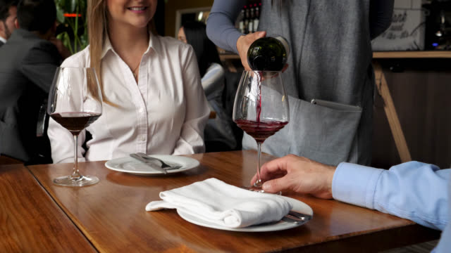 Beautiful waitress serving red wine to a customer couple at a restaurant