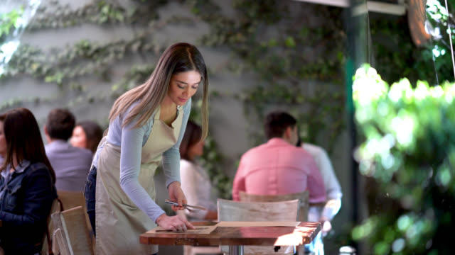 Beautiful waitress setting the table at a restaurant looking happy