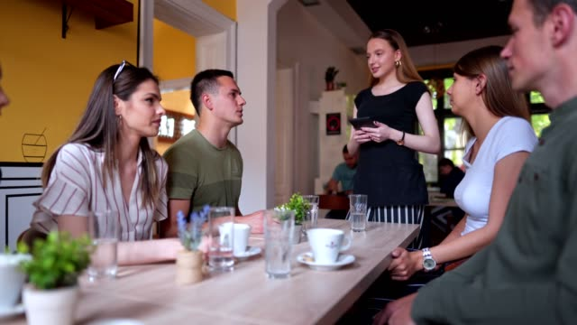 beautiful waitress taking a order from one of the tables - maschi video stock e b–roll