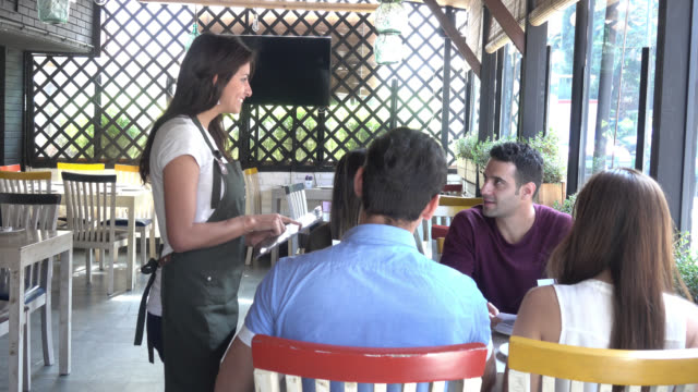 beautiful waitress taking the order of a group on a tablet - ordine video stock e b–roll
