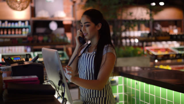 vídeos de stock e filmes b-roll de beautiful waitress talking with customer on phone and adding order to the system for takeout - trabalho no comércio