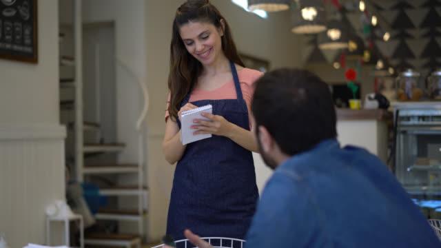 vackra servitrisen gå upp till en kund tittar på sin smartphone och erbjuda produkter till bageriet - servitris bildbanksvideor och videomaterial från bakom kulisserna