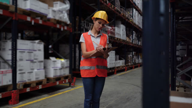 beautiful warehouse distribution worker doing inventory writing down on document very cheerfully - world trade organisation stock videos & royalty-free footage