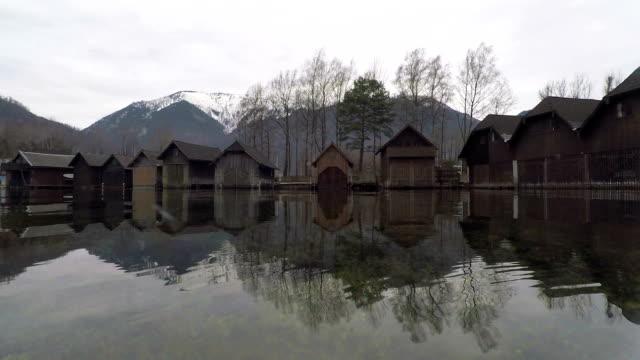 vídeos de stock, filmes e b-roll de reflexo de água bonita de casas de madeira na água - austria