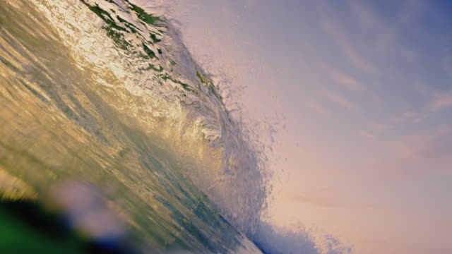 Beautiful wave POV as wave breaks over camera on shallow sand beach in the California summer sunset. Shot in slowmo.