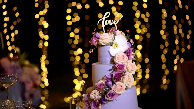 beautiful wedding cake decorated with flowers and purple tone. - figurine stock videos and b-roll footage
