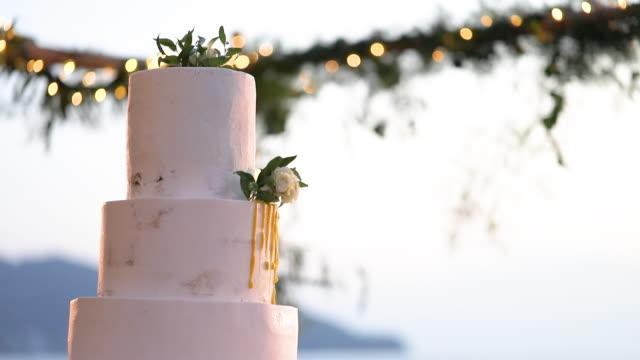 vidéos et rushes de beau gâteau de mariage décoré avec des fleurs et le ton blanc. - le marié