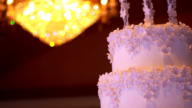 Beautiful white wedding cake with chandelier on background with copy space