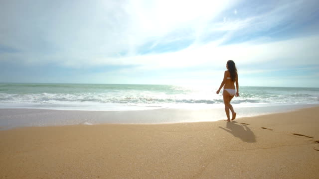 Beautiful woman alone in an amazing and unspoiled beach in the spain coast