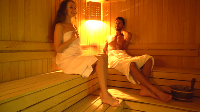 beautiful woman and man sitting in finnish sauna and relaxation - sauna stock videos & royalty-free footage