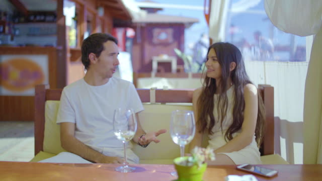 beautiful woman and young man chatting in a restaurant - silvestre stock-videos und b-roll-filmmaterial