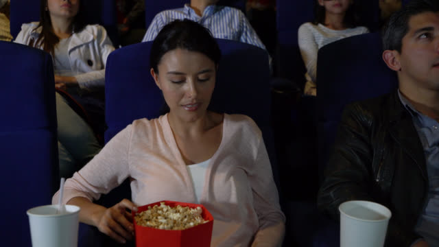 beautiful woman answering her smartphone during the movie and then hanging up while enjoying snacks - hanging up stock videos & royalty-free footage