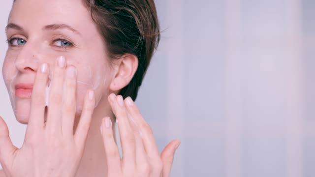 vidéos et rushes de beautiful woman applying a foam cleanser to her face - masser