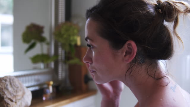 vídeos de stock e filmes b-roll de beautiful woman applying face cream in bathroom. - beleza natural pessoas