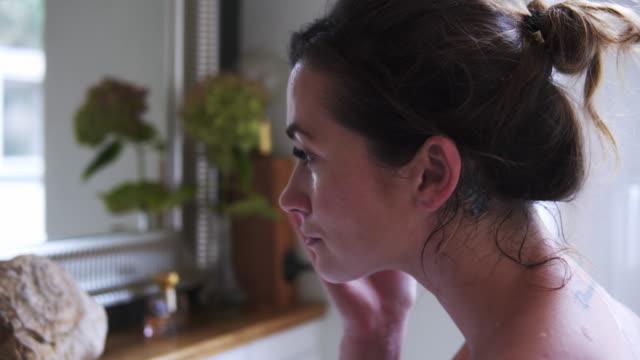 beautiful woman applying face cream in bathroom. - viso naturale video stock e b–roll