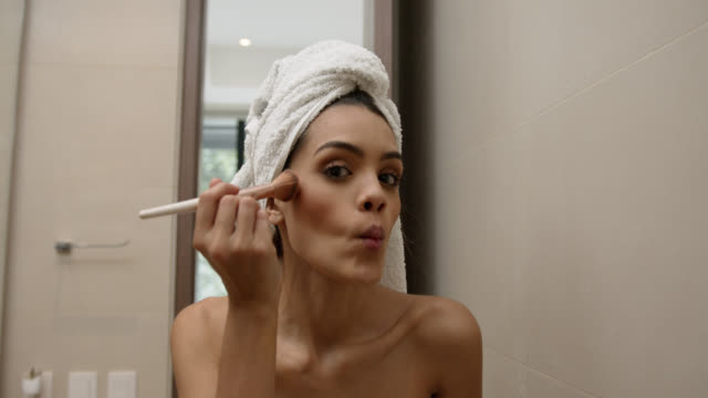 beautiful woman applying make up very cheerfully while looking at camera - domestic bathroom stock videos & royalty-free footage
