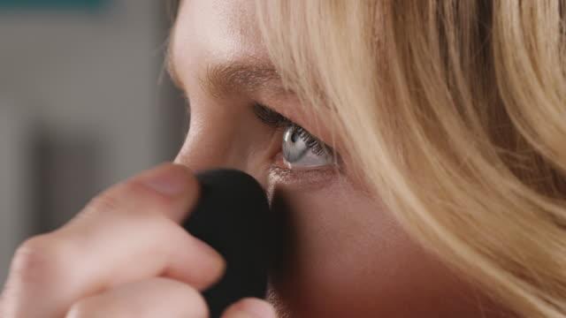 Beautiful woman applying make-up with sponge