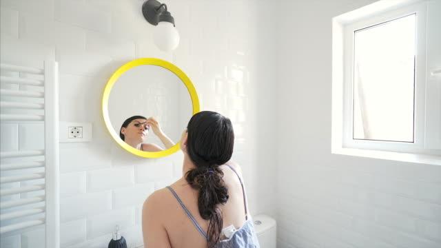 Schöne Frau Anwendung Mascara im Badezimmer.