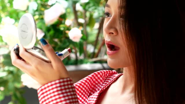vídeos y material grabado en eventos de stock de hermosa mujer aplicar maquillaje orgánico, ingrediente del concepto de rosa mosqueta - beige