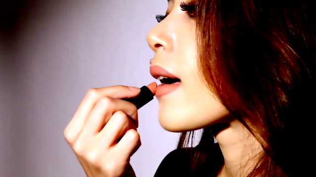 Beautiful woman applyling lipstick