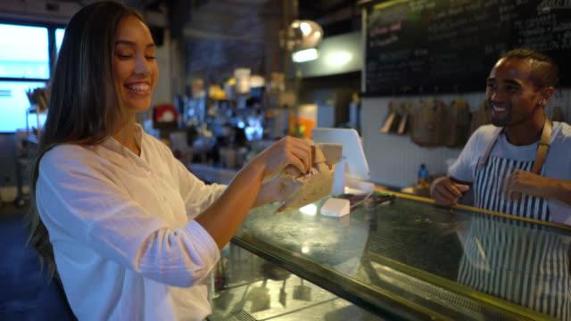 schöne frau in einer bäckerei erhalten ihr futter für nehmen sie mit einem kaffee aus der freundliche verkäufer gehen - papiertüte stock-videos und b-roll-filmmaterial