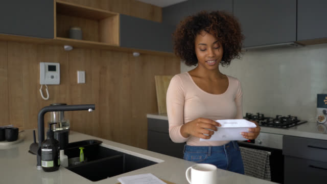 beautiful woman at home checking her mail opening an envelope - letter document stock videos & royalty-free footage