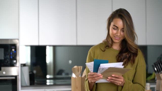 stockvideo's en b-roll-footage met mooie vrouw thuis het controleren van haar mail zeer vrolijk - brievenbus huis
