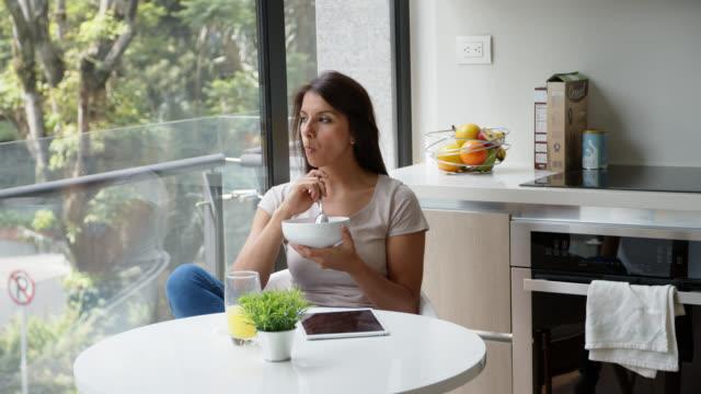 schöne frau zu hause essen eine schüssel müsli beim blick auf die fensteransicht. - freshness stock-videos und b-roll-filmmaterial
