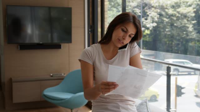 vidéos et rushes de belle femme à la maison sur un appel téléphonique avec des services à la clientèle tout en regardant les relevés bancaires - surchargé de travail