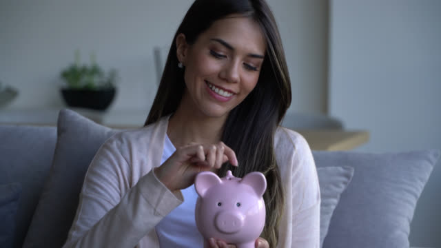 beautiful woman at home putting coins into her piggy bank while sitting on couch very happy - savings stock videos & royalty-free footage