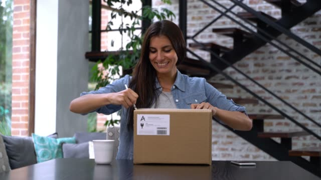 beautiful woman at home receiving a parcel and opening box very happy - package stock videos & royalty-free footage
