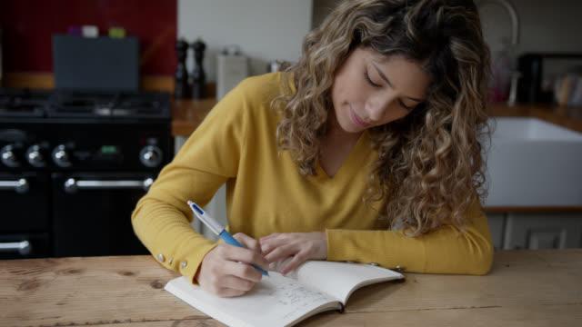 vidéos et rushes de belle femme à la maison écrivant sur son journal regardant pensif - carnet