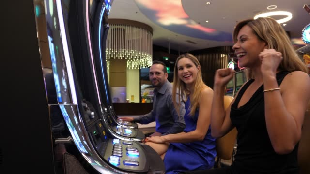 beautiful woman at the casino celebrating a win on slot machines applauding and smiling - casinò video stock e b–roll