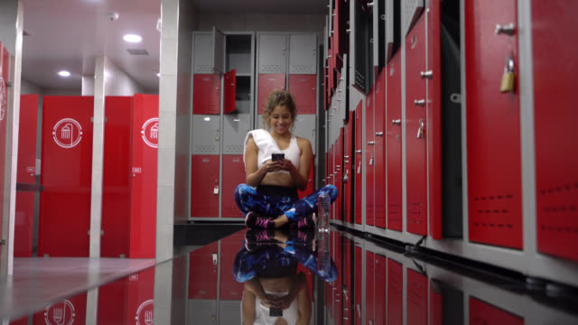 beautiful woman at the locker room gym relaxing talking on phone and then hanging up to chat online - hanging up stock videos & royalty-free footage