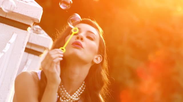 Beautiful woman blows bubbles 4